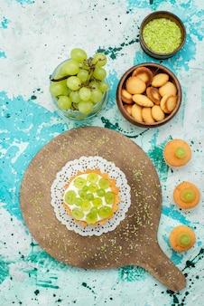 Vue de dessus du petit gâteau délicieux avec de la crème délicieuse et des biscuits aux raisins frais et tranchés isolés sur un bureau bleu clair, gâteau aux fruits sucrés
