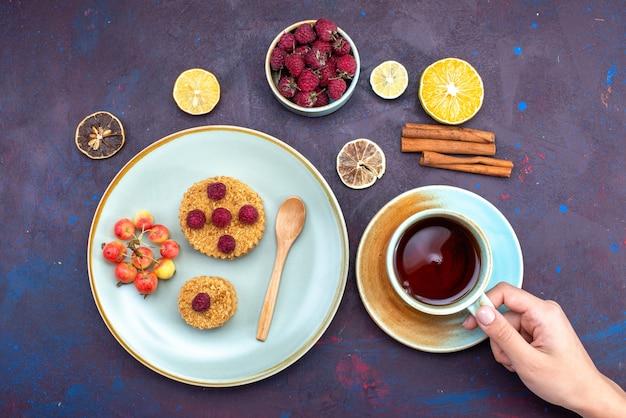 Vue de dessus du petit gâteau rond avec des framboises fraîches à l'intérieur de la plaque avec des fruits thé à la cannelle sur la surface sombre
