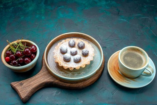 Vue de dessus du petit gâteau avec de savoureuses cerises à côté de latte sur bleu foncé,