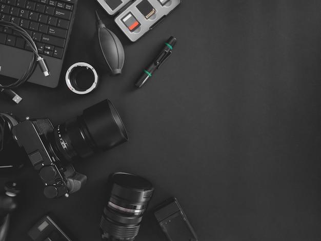 Vue de dessus du photographe de l'espace de travail avec appareil photo numérique, flash, kit de nettoyage, carte mémoire, trépied et accessoire d'appareil photo sur fond de tableau noir
