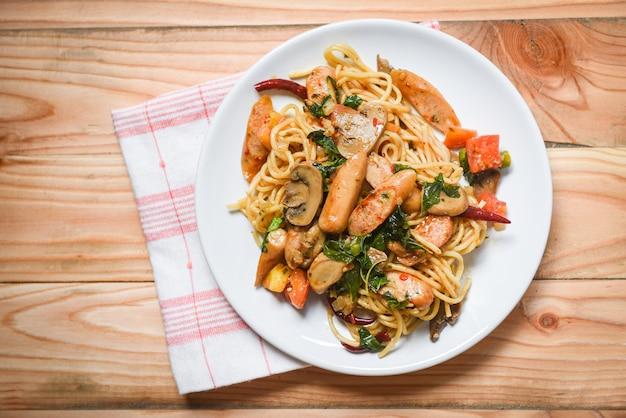 Vue de dessus du piment et du basilic avec des tomates, des pâtes et des spaghettis chauds et épicés