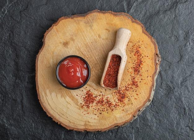 Vue de dessus du piment rouge avec du ketchup sur planche de bois.