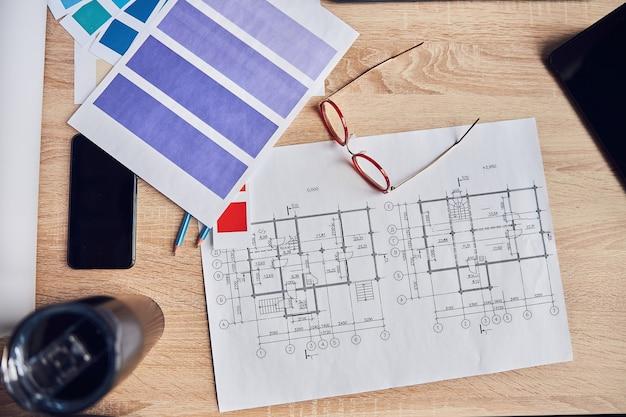 Vue de dessus du plan architectural de lunettes avec des échantillons de couleurs smartphone et crayons sur le bureau