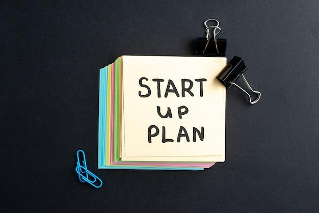 Vue de dessus du plan de démarrage écrit sur de petites feuilles de notes outils de bureau simples sur fond noir avec espace libre