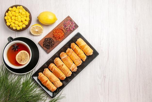 Vue de dessus du plat de loin sur le conte en bois avec des branches d'arbres à côté de la tasse de thé noir avec des bols de citron de bonbons et d'épices citron à côté de l'assiette de pâte tubulaire sur la table