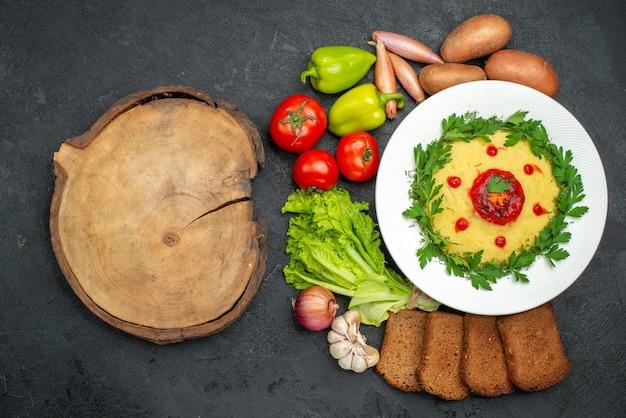 Vue de dessus du plat de pommes de terre en purée avec des miches de pain noir et des légumes sur noir