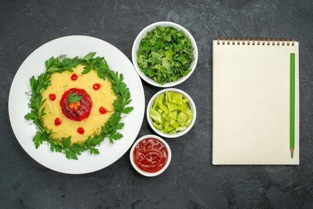 Vue de dessus du plat de pommes de terre en purée avec sauce tomate et légumes verts sur noir