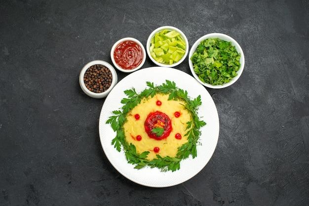 Vue de dessus du plat de pommes de terre en purée avec des verts sur noir