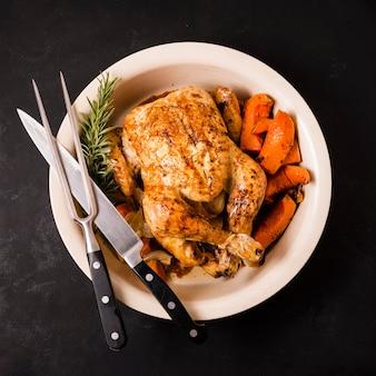 Vue de dessus du plat de poulet rôti de thanksgiving avec des couverts
