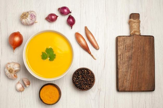 Vue de dessus du plat texturé à la crème de soupe à la citrouille savoureuse sur blanc clair
