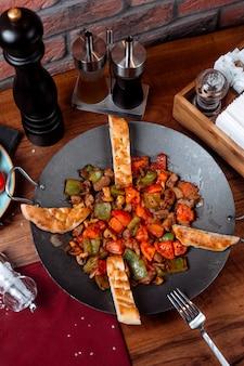Vue de dessus du plat traditionnel azerbaïdjanais saj kebab avec des morceaux de champignons de viande et de légumes sur la table