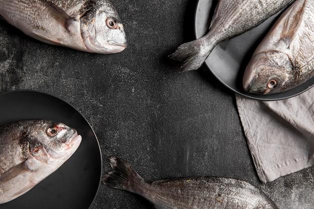 Vue de dessus du poisson sur assiette et tissu