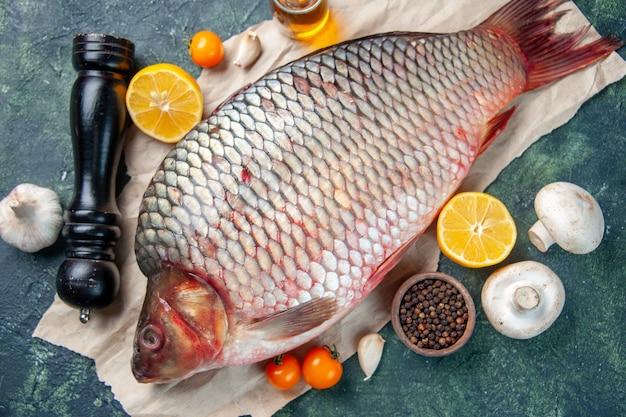 Vue de dessus du poisson cru frais aux champignons et assaisonnements sur fond bleu foncé