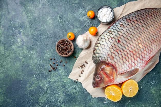 Vue de dessus du poisson cru frais avec du poivre et du citron sur fond bleu foncé