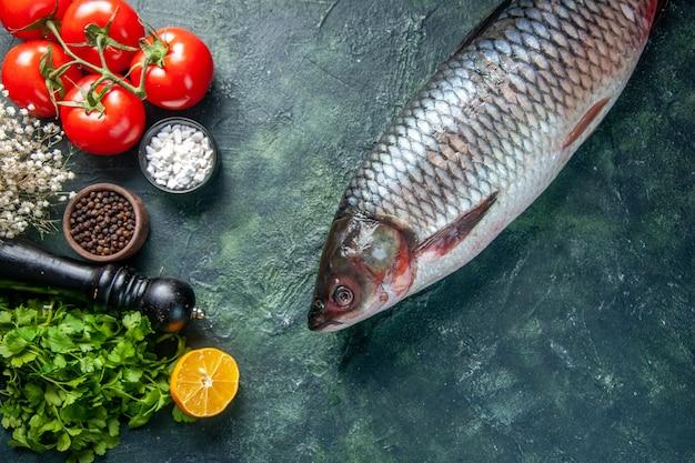 Vue de dessus du poisson cru frais avec des légumes verts et des tomates sur fond sombre