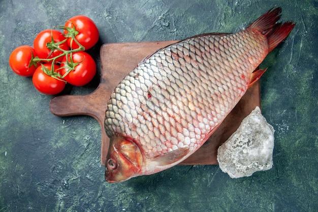 Vue de dessus du poisson cru frais sur une planche à découper fond bleu foncé