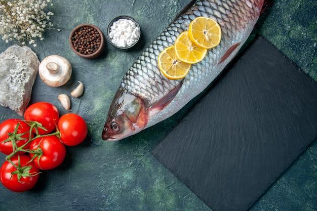 Vue de dessus du poisson cru frais avec des tranches de citron et des tomates sur fond bleu foncé