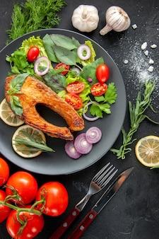 Vue de dessus du poisson cuit savoureux avec des légumes frais sur la table sombre