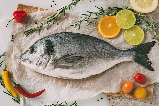 Vue de dessus du poisson dorade sur une plaque à pâtisserie avec romarin, citron, orange, tomate