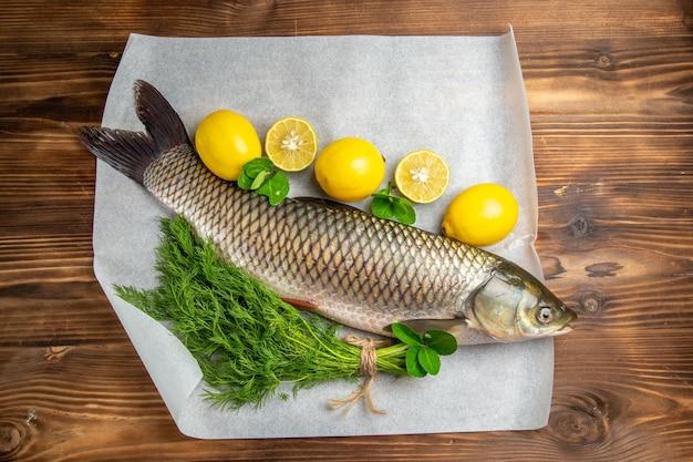 Vue de dessus du poisson frais avec des citrons et des verts sur un bureau marron