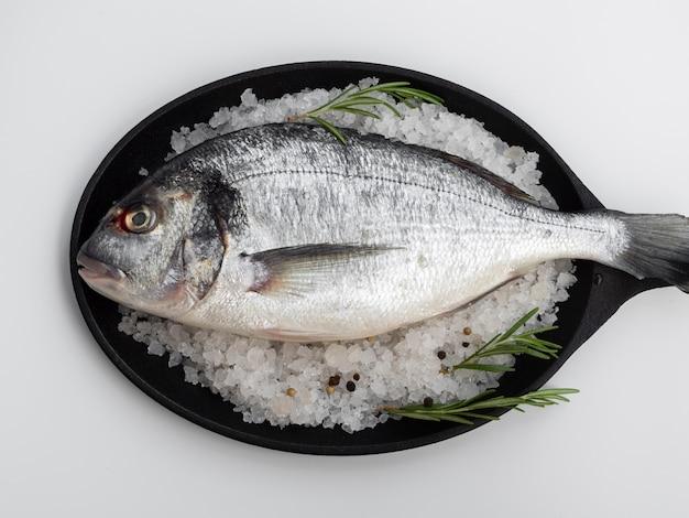 Vue de dessus du poisson frais dans une casserole avec des herbes