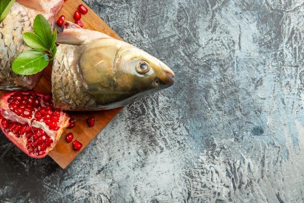 Vue de dessus du poisson frais en tranches avec des grenades sur une surface clair-sombre