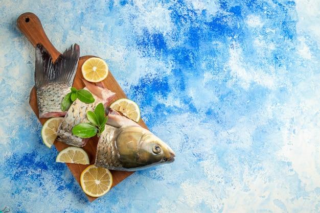 Vue de dessus du poisson frais en tranches avec des tranches de citron sur la surface bleue