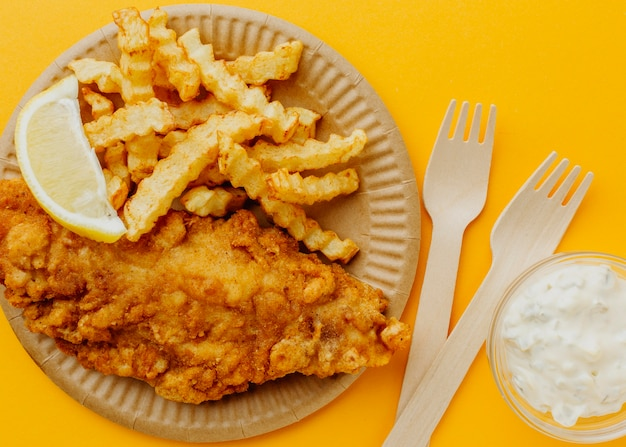 Vue de dessus du poisson-frites avec fourchettes et citron