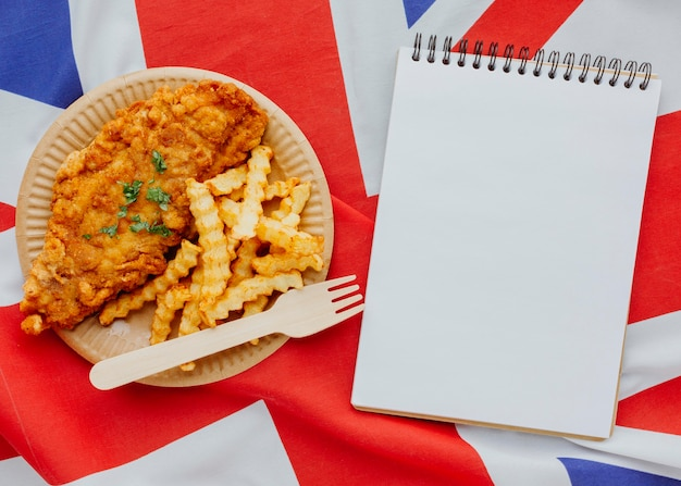 Vue de dessus du poisson-frites sur plaque avec ordinateur portable et drapeau de la grande-bretagne