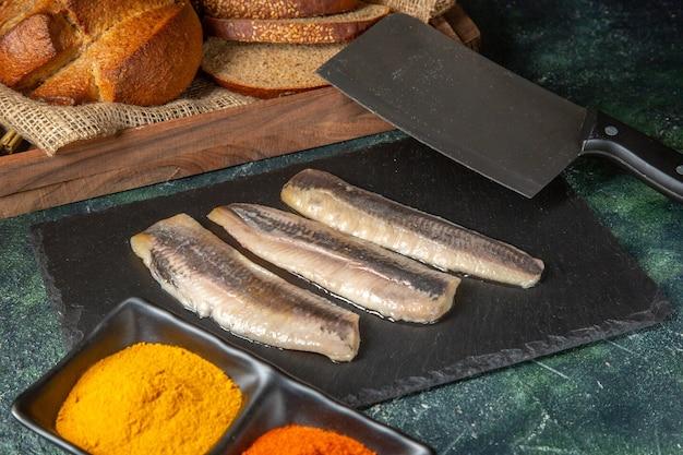 Vue de dessus du poisson haché cru frais sur planche à découper en bois noir épices couperet à pain