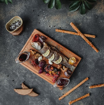 Vue de dessus du poisson rôti avec des légumes au citron et une sauce à la grenade narsharab sur une planche de bois sur un mur sombre
