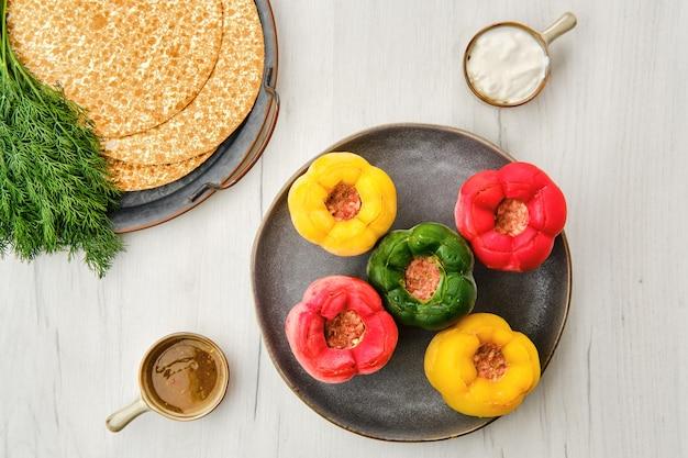Vue de dessus du poivron coloré farci de viande et de riz sur une table en bois blanc