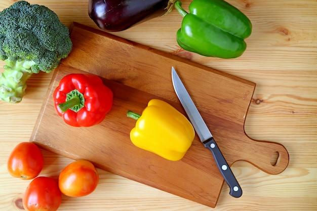 Vue de dessus du poivron jaune sur une planche à découper avec un couteau et un autre légumes