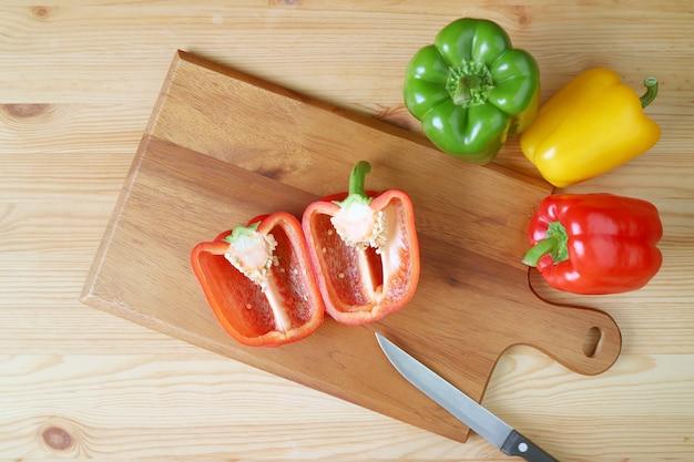 Vue de dessus du poivron rouge coupé sur une planche à découper avec couteau