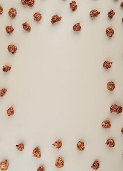 Vue de dessus du pop-corn au chocolat sur blanc avec espace copie