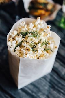Vue de dessus du pop-corn au romarin dans un sac en papier sur la table en marbre.
