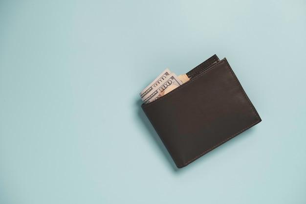 Vue de dessus du portefeuille d'argent en cuir marron avec billet isolé sur bleu.