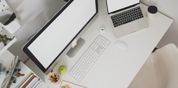 Vue de dessus du poste de graphiste avec un ordinateur portable à écran blanc