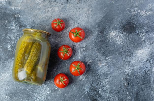 Vue de dessus du pot de cornichon et des tomates fraîches.