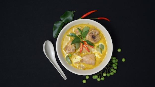 Vue de dessus du poulet au curry vert et ingrédients sur fond de bureau noir