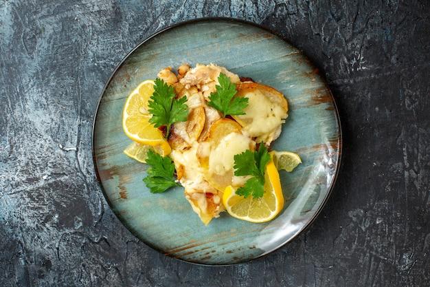 Vue de dessus du poulet avec du fromage sur un plateau sur une table sombre