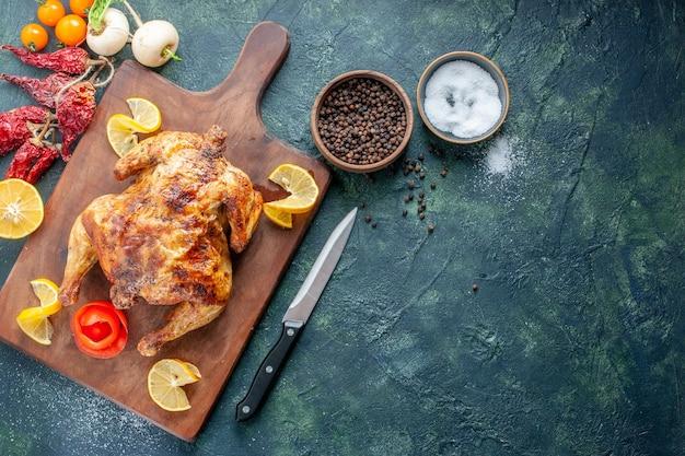 Vue de dessus du poulet épicé cuit avec des tranches de citron sur une surface sombre