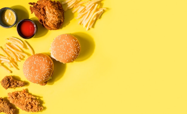 Vue de dessus du poulet frit, des hamburgers et des frites avec copie-espace
