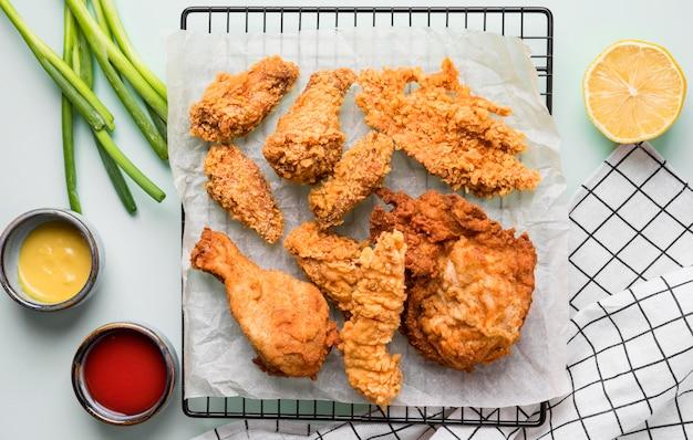 Vue de dessus du poulet frit sur le plateau avec des sauces, des oignons verts et du citron