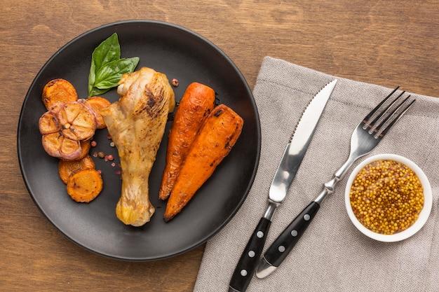 Vue de dessus du poulet et des légumes cuits au four sur une assiette avec des couverts et de la moutarde de dijon