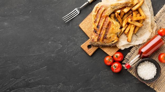 Vue de dessus du poulet et des pommes de terre cuits au four avec des tomates et de l'espace de copie