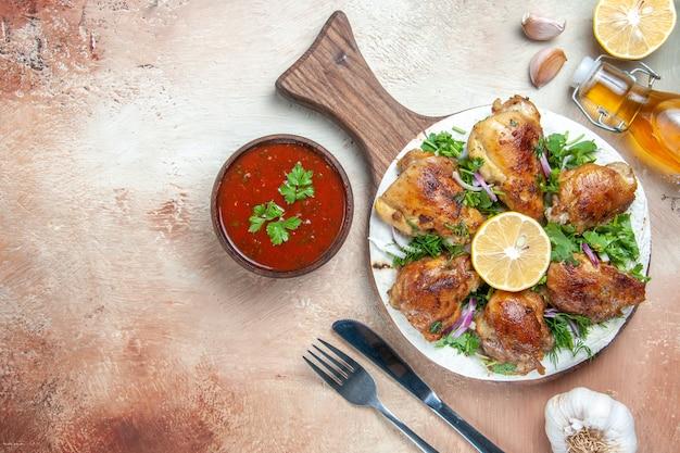 Vue de dessus du poulet poulet avec des herbes de citron oignon sur le couteau fourchette sauce huile conseil