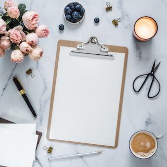 Vue de dessus du presse-papiers avec une page vide blanche. presse-papiers, fleurs, bougie parfumée sur marbre blanc.