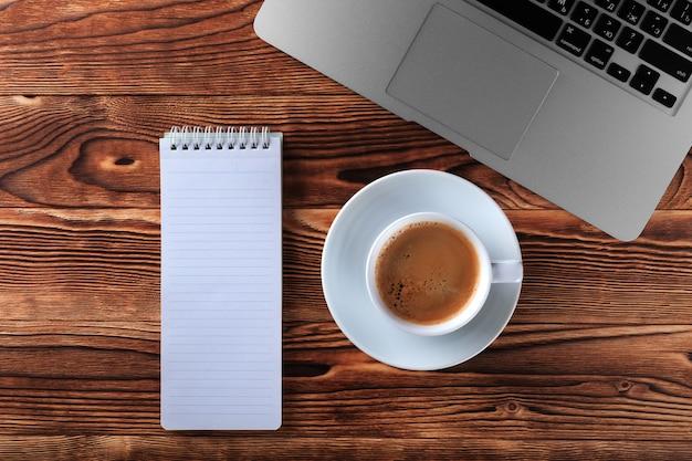 Vue de dessus du processus d'étude avec cahier, livre et ordinateur portable. tasses de café sur la table
