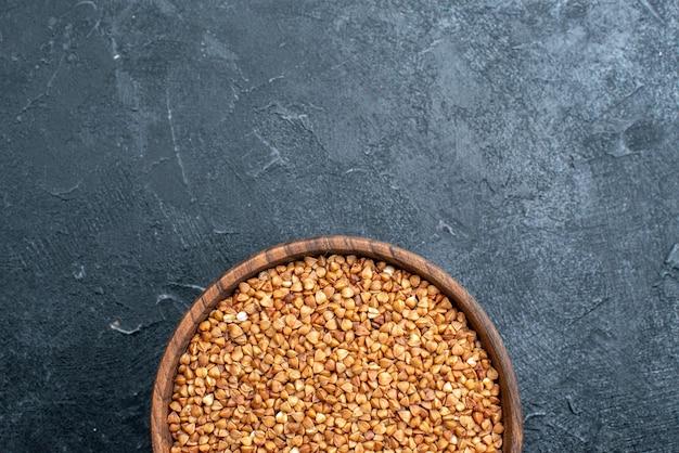 Vue de dessus du produit utile de sarrasin cru à l'intérieur de la plaque sur l'espace sombre